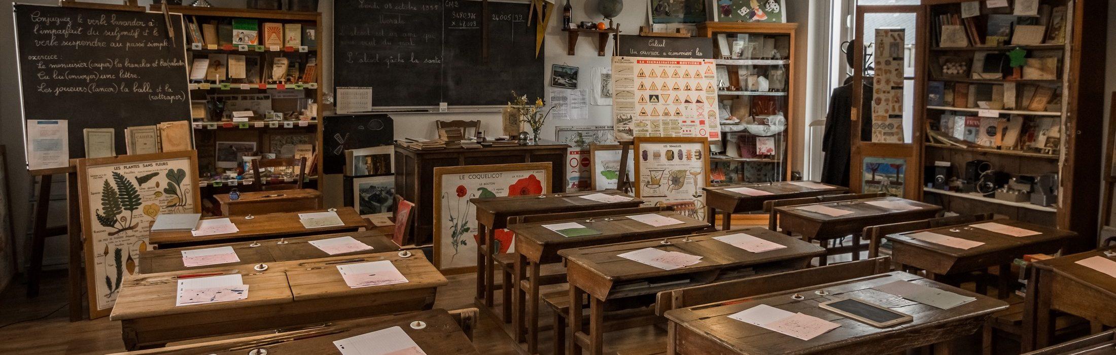 Reconstitution d'une classe des années 50 avec ses tableaux noirs, ses pupitres en bois, ses armoires remplies d'objets scolaires. Les visiteurs accueillis par 1